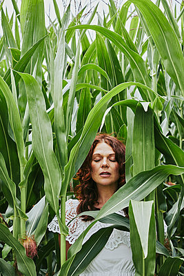 Portrait of a beautiful redheaded woman in a cornfield - p1540m2200502 by Marie Tercafs