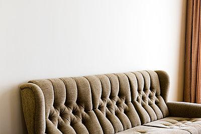 Beige Retro Couch mit brauner Gardine - p177m1087497 von Kirsten Nijhof