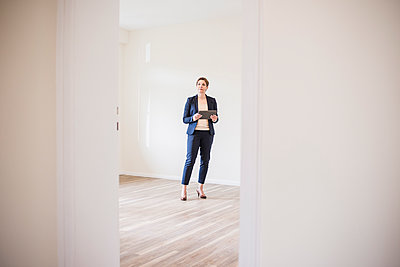 Woman in empty apartment with tablet - p300m1460596 by Uwe Umstätter