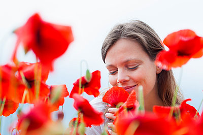 Smiling woman smelling fresh red poppy flower against sky - p300m2197483 by Daniel Ingold