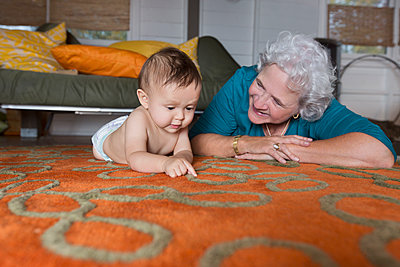 Grandmother and grandson laying on carpet - p555m1231762 by Jasper Cole