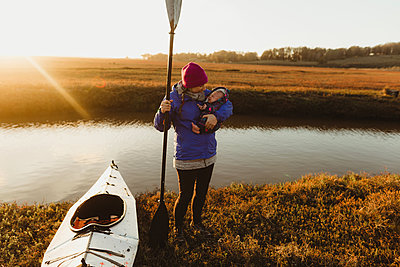 Woman kayaker on riverbank carrying baby daughter at sunset, Morro Bay, California, USA - p924m1494858 by Peter Amend