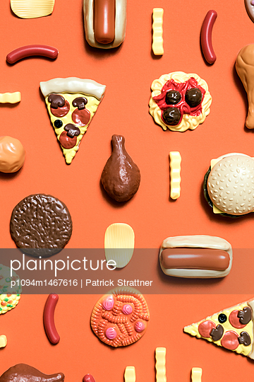 Directly above shot of various fast food toys on orange background - p1094m1467616 by Patrick Strattner