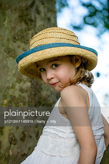 Mädchen mit Sonnenhut auf einem Baum - p1212m1145916 von harry + lidy