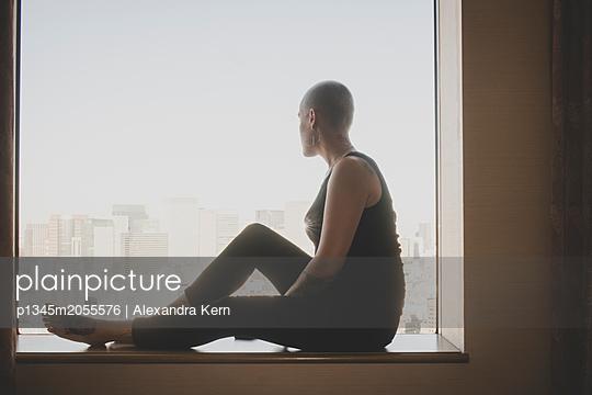 Frau sitzt auf dem Fensterbrett - p1345m2055576 von Alexandra Kern