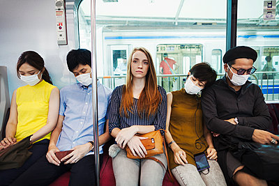 Five people wearing dust masks sitting sidy by side on a subway train, Tokyo commuters.  - p1100m1531107 by Mint Images