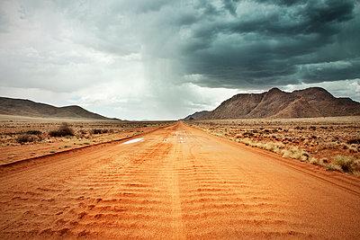 sandige rote Straße mit starkem Regen und Gewitter am Horizont, Tiras Gebirge, Tirasberge, Namib Naukluft Park, Namibia, Afrika - p1316m1160898 von Günther Bayerl
