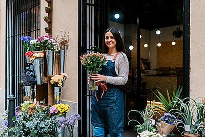 Young female florist holding flower vase while standing at shop - p300m2274932 by Ezequiel Giménez