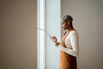 Woman using digital tablet at home - p300m2277408 by Rafa Cortés