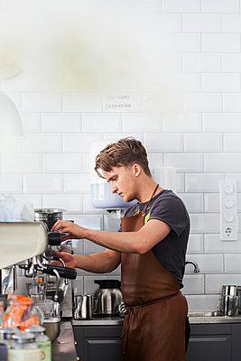 Barista making coffee using espresso machine at restaurant - p426m977413f by Astrakan