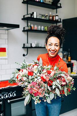 Portrait of mid adult female florist holding flower bouquet in florists workshop - p429m1418063 by Alys Tomlinson