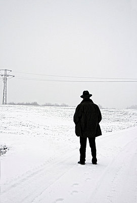 Man in black jacket and hat standing on snowy road - p476m1162906 by Ilona Wellmann