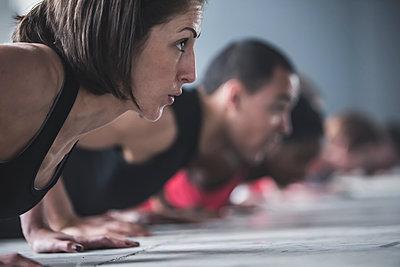 Close up of athletes doing push-ups on floor - p555m1411990 by John Fedele