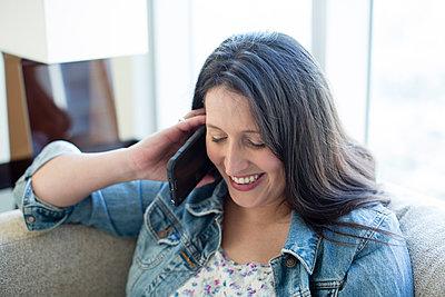 Hispanic woman talking on cell phone on sofa - p555m1412048 by Deborah Kolb