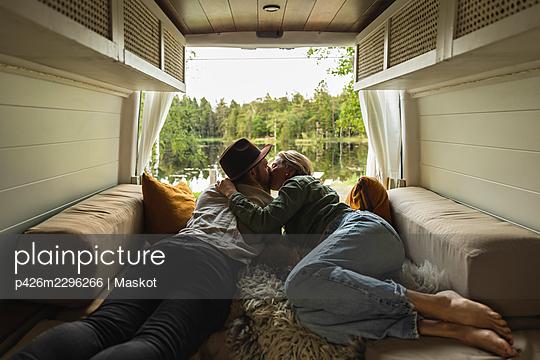 Girlfriend kissing boyfriend while lying down in motor home - p426m2296266 by Maskot