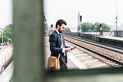 Businessman with cell phone and earphones waiting at the platform - p300m2003958 by Uwe Umstätter