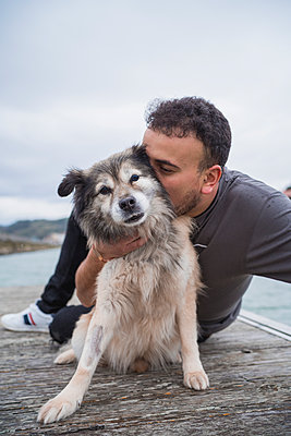 Man embracing dog while sitting on pier at beach against sky - p300m2257274 by SERGIO NIEVAS