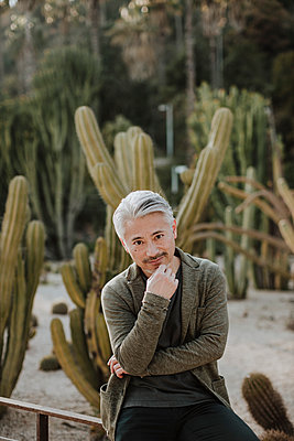 Smiling mature man sitting on railing with cactus plants in background at garden - p300m2276157 by Gala Martínez López