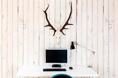 Home office with personal computer and deer antler hanging on wooden wall - p300m940894f by Stefan Rupp