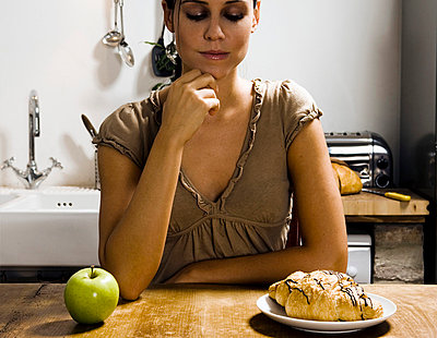 Woman at table with apple and pastry. - p4291429f by Chev Wilkinson