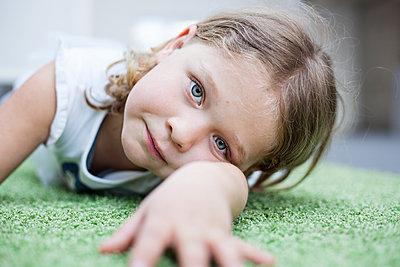 Mädchen liegt auf dem Fußboden - p712m1466292 von Jana Kay