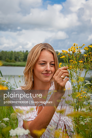 Blonde woman picking wild flowers - p1093m2193608 by Sven Hagolani