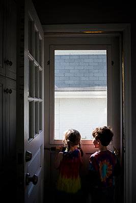 Rear view of siblings looking through window while standing at home - p1166m1474044 by Cavan Images