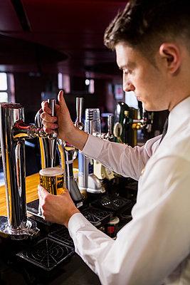 Well dressed bartender serving beer  - p1315m1186439 by Wavebreak