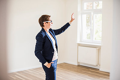 Woman in empty apartment wearing smartglasses - p300m1459906 by Uwe Umstätter