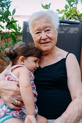Portrait of smiling Grandmother spending tome with her graddaughter on terrace - p300m2029196 by Gemma Ferrando