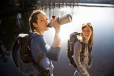 Two women sharing water beside lake - p4297910 by Hugh Whitaker