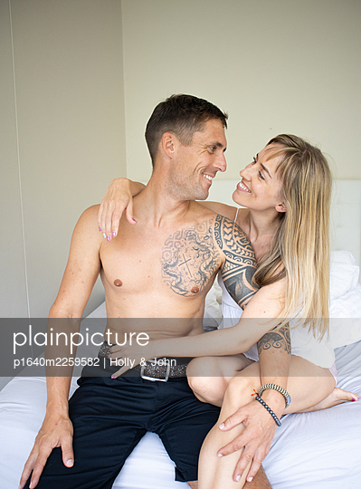 Couple in love sitting on bed, portrait - p1640m2259582 by Holly & John