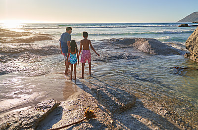 Family walking on rocks on sunny ocean beach, Cape Town, South Africa - p1023m2200861 by Trevor Adeline