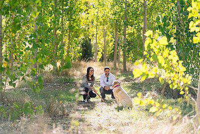 A couple playing with their dog in a park - p300m2166355 by Daniel González