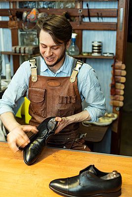 Male cobbler polishing shoe at workshop - p300m2282857 by Vladimir Godnik