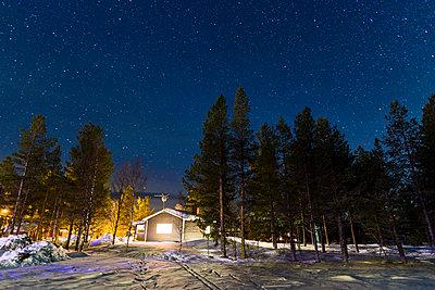 Illuminated mountain cabin at night - p312m1470597 by Mikael Svensson