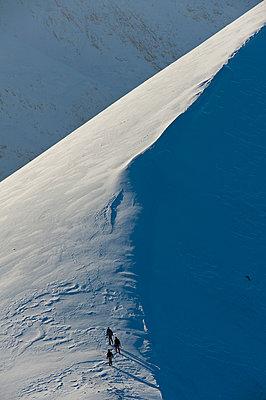 Walkers climbing snowy ridge of Sgorr Dhearg in winter near Glen Coe; Highlands, Scotland - p442m999934 by Ian Cumming
