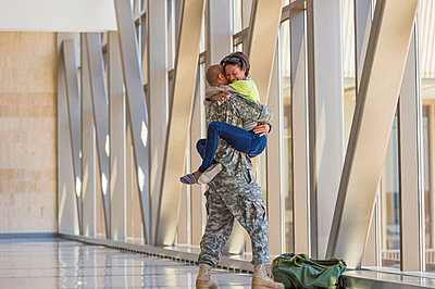 Returning soldier greeting girlfriend in airport - p555m1311964 by Mark Edward Atkinson/Tracey Lee