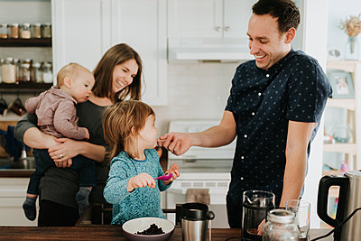 Mid adult couple with toddler daughter and baby son at kitchen table - p924m2077964 by Sara Monika