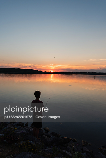 Adolescent boy fishing on shore of lake at sunset in Ontario, Canada. - p1166m2201978 by Cavan Images