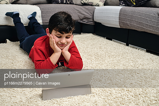 child watches a movie on his tablet - p1166m2279565 by Cavan Images