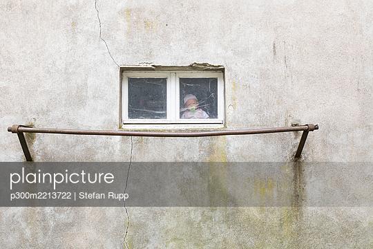 Germany, doll sitting behind window of garage - p300m2213722 by Stefan Rupp