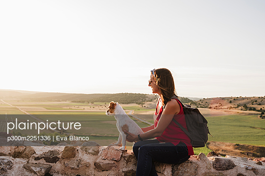 woman and dog at sunset in beautiful landscape, Soria, Spain - p300m2251336 von Eva Blanco