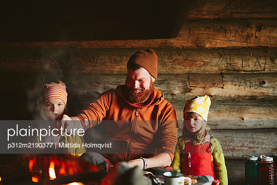 Man with daughters sitting near campfire - p312m2190377 by Matilda Holmqvist