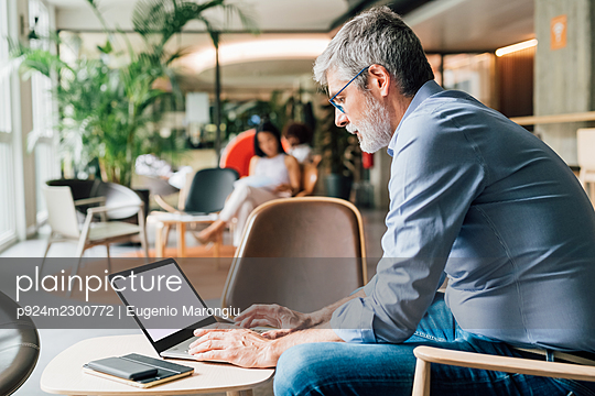 Italy, Businessman using laptop at table in creative studio - p924m2300772 by Eugenio Marongiu
