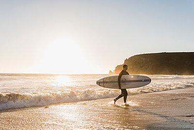 France, Bretagne, Crozon peninsula, woman walking on beach at sunset carrying surfboard - p300m1189373 by Uwe Umstätter