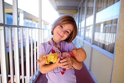 Portrait of happy girl carrying doll in corridor - p1166m1486192 by Cavan Images
