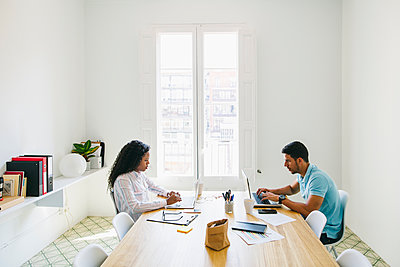 Young businessman and woman working together in office, using laptop - p300m1157169 by Bonninstudio