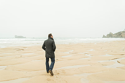 France, Bretagne, Finistere, Crozon peninsula, man walking on the beach - p300m1188542 by Uwe Umstätter