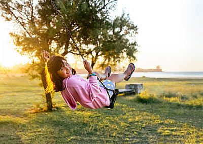 Portrait of smiling little girl on a swing in the evening - p300m1537218 by Marco Govel
